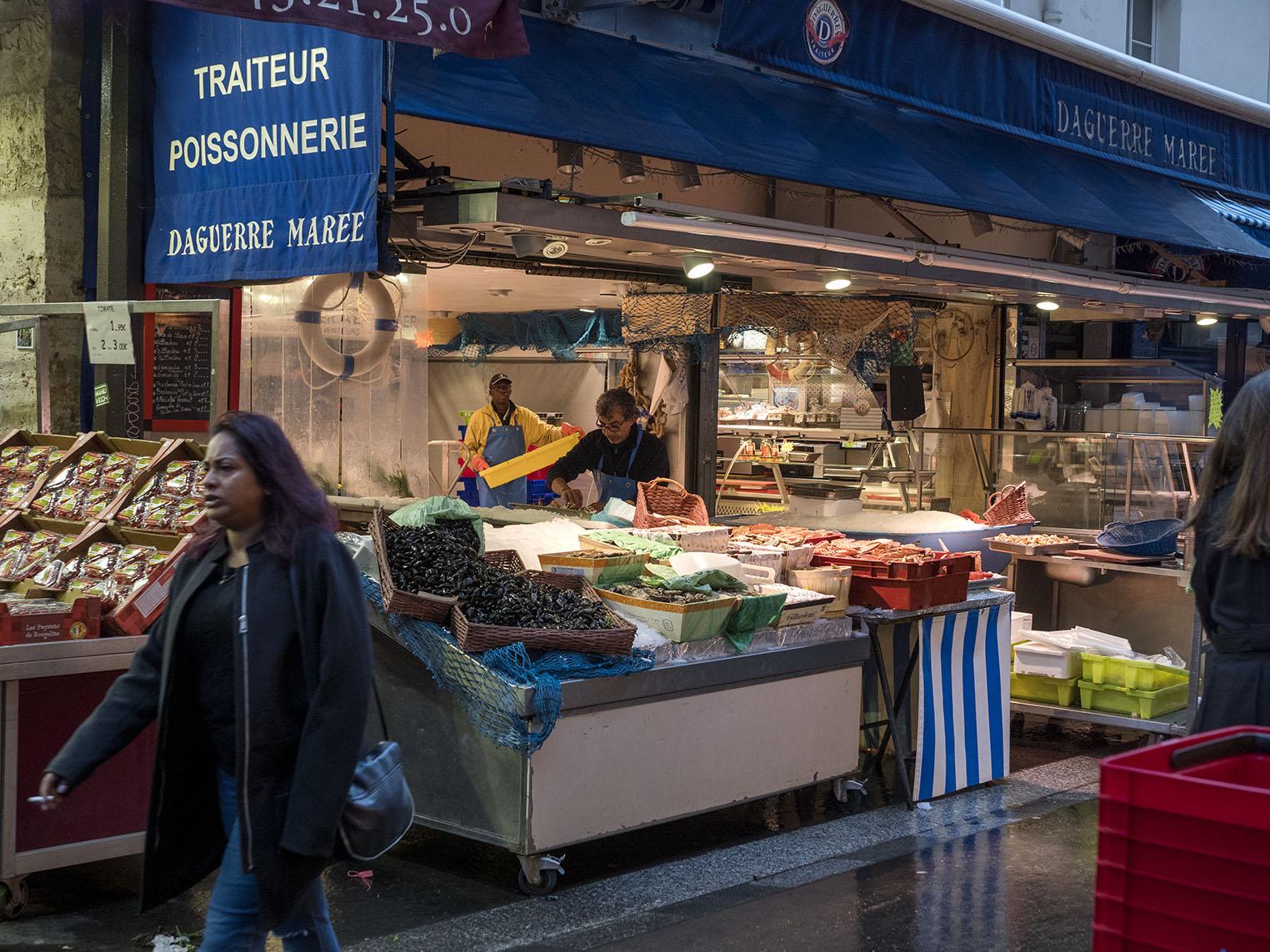 Fiskhandlaren fick sin fisk levererad under natten och dukar nu upp med havets läckerheter på rue Daguerre. Olympus OM-D E-M1 II, Zuiko 50 mm 1,2 1/125 och bländare 3,2, 800 Asa.